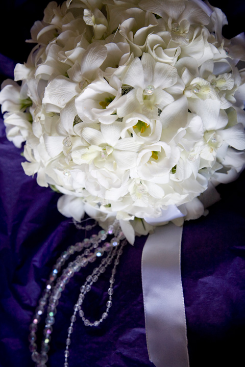 Tight posy of white Dendrobium orchids and white Eustoma