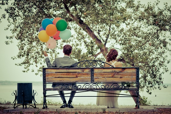 being married is awesome couple on a bench with balloons
