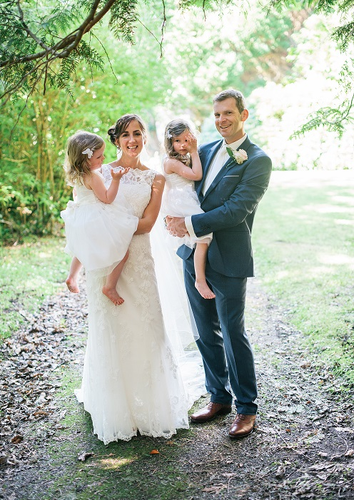 bride and groom holding kids