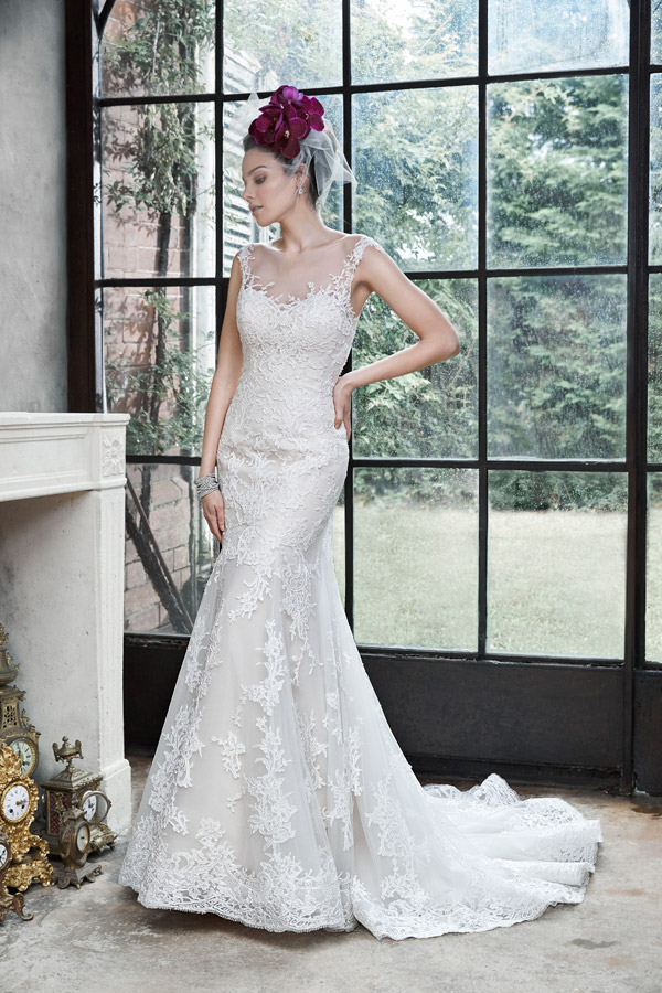 Noelle Elegant romance is found in this soft fit and flare gown, constructed of delicate tulle and lace. Finished with illusion neckline, dramatic illusion back, and pearl buttons over zipper closure.