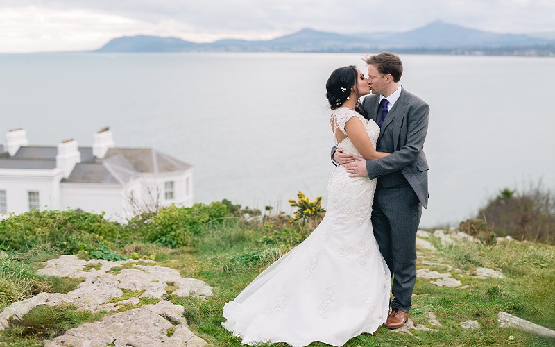 bride and groom embracing on cliff