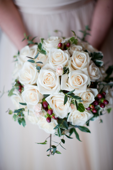 The winter berries and cream roses give this bouquet a sense of seasonal charm