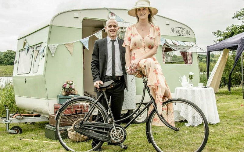 couple on bike in front of caravan