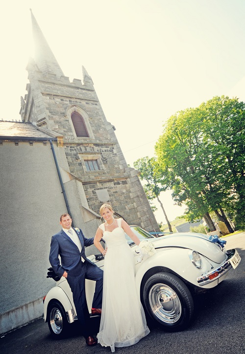 bride and groom posing on a car