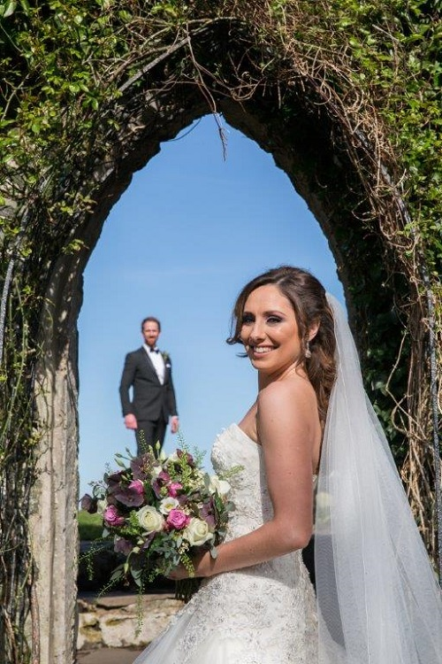 bride standing under arch with groom in the distance