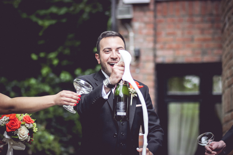 groom popping champagne