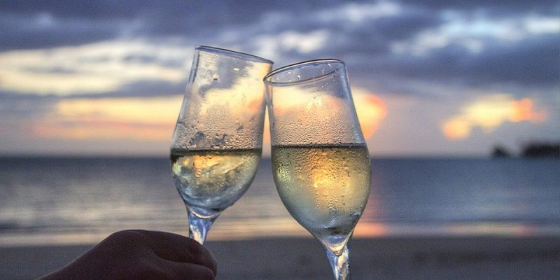 wine glasses clinking on beach