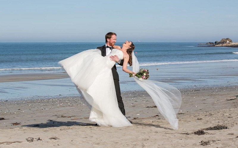 groom lifting bride on beach