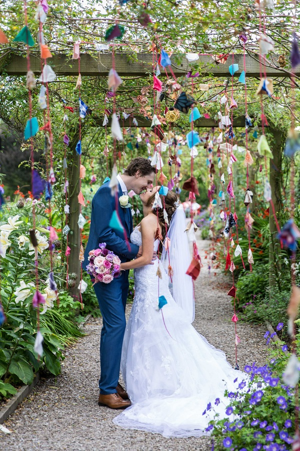 bride and groom behind origami arch