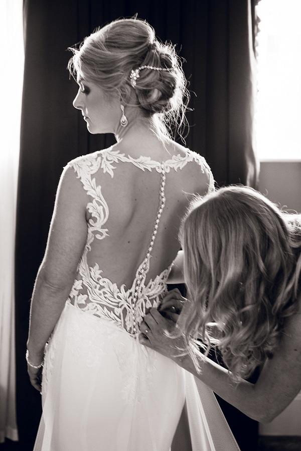 bridesmaid doing up dress of bride