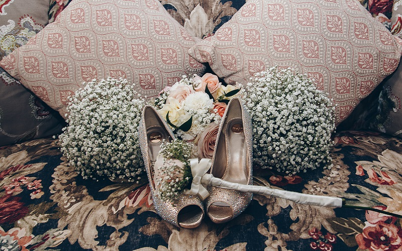 Flowers and shoes arranged on sofa